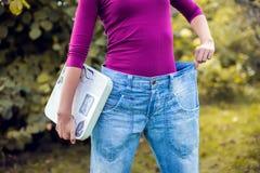 Sportliche Frau, die große Hosen zeigt und Skalen hält Gewichtsverlust c lizenzfreies stockbild