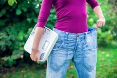 Sportliche Frau, die große Hosen zeigt und Skalen hält Gewichtsverlust c lizenzfreie stockbilder