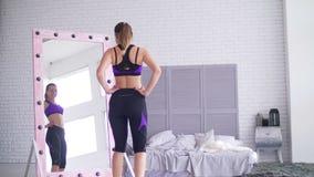 Sportliche Frau, die ihre Körperform im Spiegel bewundert stock video