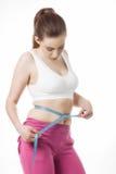 Sportliche Frau, die ihre Taille misst Stockbilder