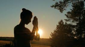 Sportliche Frau, die im Park bei Sonnenuntergang betet stock video footage