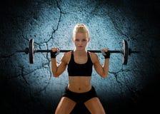 Sportliche Frau, die mit Barbell trainiert Stockfotos