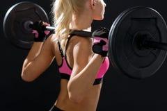 Sportliche Frau, die mit Barbell von der Rückseite trainiert Lizenzfreie Stockfotos