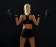 Sportliche Frau, die mit Barbell von der Rückseite trainiert Stockfotografie