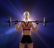 Sportliche Frau, die mit Barbell von der Rückseite trainiert Stockfotos