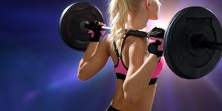 Sportliche Frau, die mit Barbell von der Rückseite trainiert Stockfoto