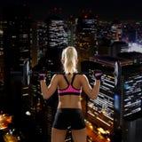 Sportliche Frau, die mit Barbell von der Rückseite trainiert Lizenzfreie Stockfotografie