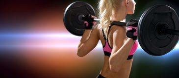 Sportliche Frau, die mit Barbell von der Rückseite trainiert Stockbilder