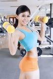 Sportliche Frau, die mit Dummköpfen trainiert lizenzfreie stockfotos