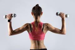 Sportliche Frau, die mit Gewichten ausarbeitet Rückseitige Ansicht lizenzfreie stockfotos