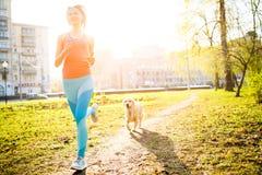 Sportliche Frau, die mit Hund läuft Stockfoto