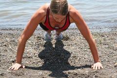 Sportliche Frau, die Pushups tut Lizenzfreie Stockfotografie