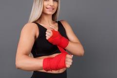 Sportliche Frau, die roten Verband einwickelt Lizenzfreie Stockfotos