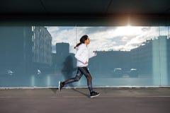 Sportliche Frau, die in die Stadt läuft und trainiert Stockbild