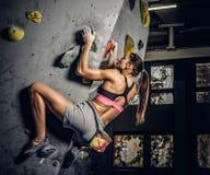 Sportliche Frau, die zuhause künstlichen Flussstein klettert lizenzfreies stockfoto