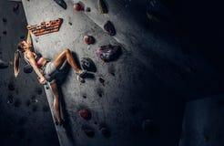 Sportliche Frau, die zuhause künstlichen Flussstein klettert lizenzfreie stockfotografie
