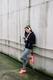 Sportliche Frau mit den headhphones, die auf Smartphone simsen Lizenzfreie Stockbilder