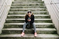 Sportliche Frau mit den headhphones, die auf Smartphone simsen Stockfotos