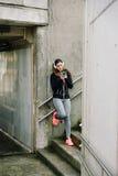 Sportliche Frau mit den headhphones, die auf Smartphone simsen Lizenzfreies Stockfoto