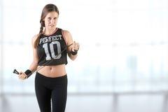 Sportliche Frau mit einem springenden Seil, lokalisiert im Weiß lizenzfreie stockfotos