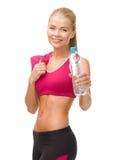 Sportliche Frau mit Flasche des Wassers und des Tuches Stockfotografie