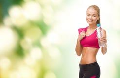 Sportliche Frau mit Flasche des Wassers und des Tuches Lizenzfreie Stockfotografie