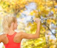Sportliche Frau mit schwerem Stahldummkopf von der Rückseite Stockfotografie