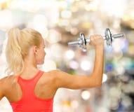 Sportliche Frau mit schwerem Stahldummkopf von der Rückseite Stockbild