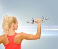 Sportliche Frau mit schwerem Stahldummkopf von der Rückseite Lizenzfreies Stockfoto