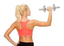 Sportliche Frau mit schwerem Stahldummkopf von der Rückseite Lizenzfreie Stockfotografie