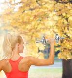 Sportliche Frau mit schwerem Stahldummkopf von der Rückseite Stockbilder