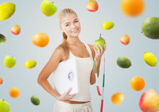 Sportliche Frau mit Skala, Apfel und messendem Band Lizenzfreie Stockbilder