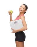 Sportliche Frau mit Skala und grünem Apfel Stockfotos
