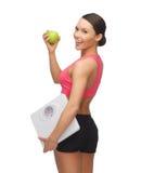 Sportliche Frau mit Skala und grünem Apfel Lizenzfreie Stockfotos
