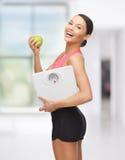 Sportliche Frau mit Skala und grünem Apfel Lizenzfreie Stockbilder