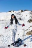 Sportliche Frau in Ski Gear mit Ausrüstung am Schnee Stockfotografie