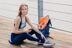 Sportliche Frau trägt zufällige Spitze, Gamaschen und sportshoes, Blicke positiv an der Kamera, Griffhandy in den Händen, hört Ra lizenzfreie stockbilder