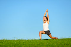 Sportliche Frau, welche die Arme und Beine im Freien ausdehnt Stockfoto
