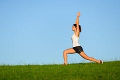 Sportliche Frau, welche die Arme und Beine im Freien ausdehnt lizenzfreie stockfotos
