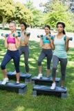Sportliche Frauen, die Stepp-Aerobic mit Dummköpfen tun Stockfoto