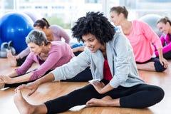 Sportliche Frauen, die Zehen berühren Stockfoto