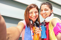 Sportliche Freundinnen, die selfie während eines Bruches an Lauftraining nehmen Stockbild