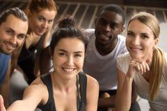 Sportliche gemischtrassige Freunde, die Gruppe selfie hält das Schauen von a nehmen stockfotografie
