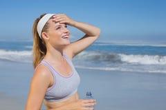 Sportliche glückliche blonde Stellung auf dem Strand Stockbild