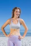 Sportliche glückliche blonde Stellung auf dem Strand Stockfotografie