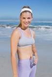 Sportliche glückliche blonde Stellung auf dem Strand mit Flasche Stockfoto