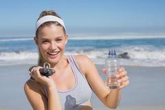 Sportliche glückliche blonde Stellung auf dem Strand mit Flasche und Springseil Lizenzfreies Stockbild