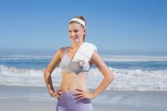 Sportliche glückliche blonde Stellung auf dem Strand mit Tuch Stockfotos