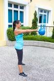 sportliche hispanische Frau im blauen Training mit dem kettlebell, welches das Schwingenprogramm tut Lizenzfreies Stockbild