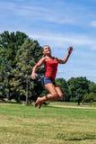 Sportliche junge blonde Frau, die draußen für Glück springt Lizenzfreies Stockbild